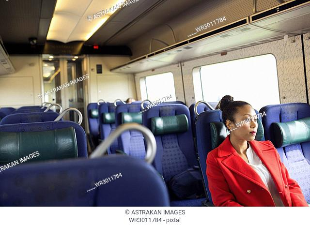 Woman in red coat sitting alone in train