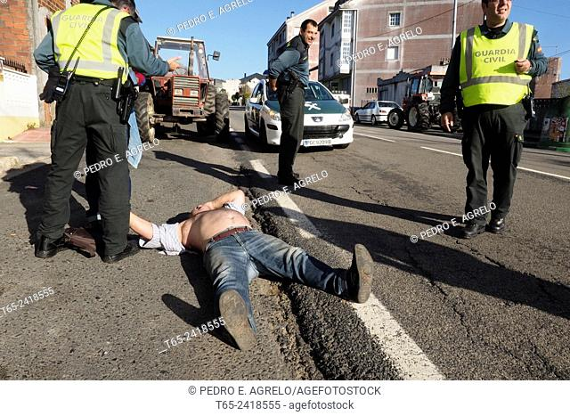 27 October 2014. A man cries and laments received a beating. After the fight, he remains lying on the ground and too close to a major road, in Lugo, Galicia