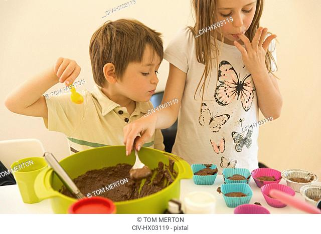 Boy and girl brother and sister making chocolate cupcakes, licking fingers