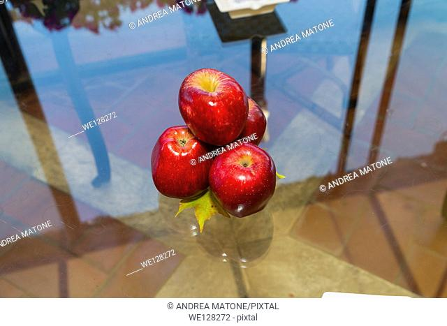 Red apples on a glass table