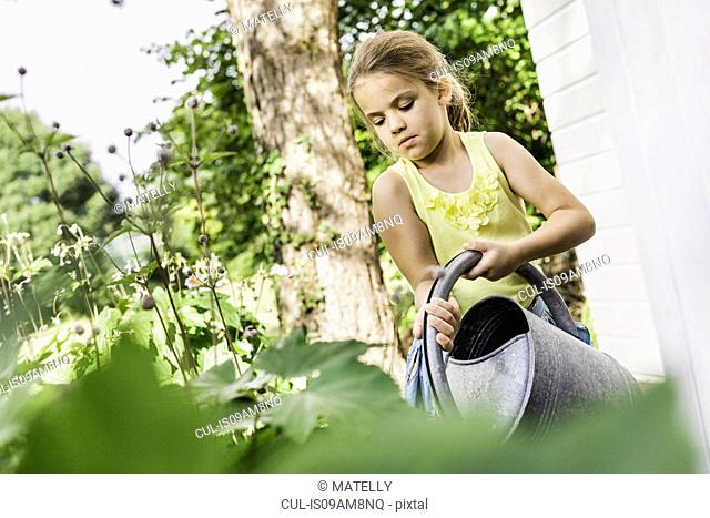 Girl concentrating whilst watering plants in garden