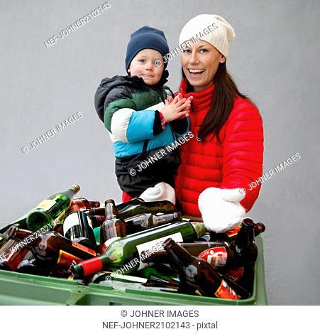 Mother with boy near recycling bin