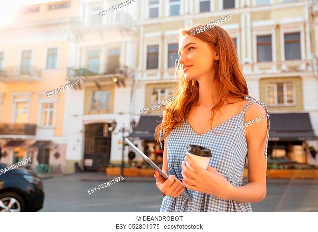 Young pretty girl holding pc tablet and cup of coffee while walking outdoors at the city street