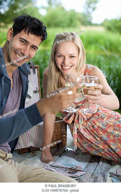 Young couple picnicking and toasting wine glasses in park