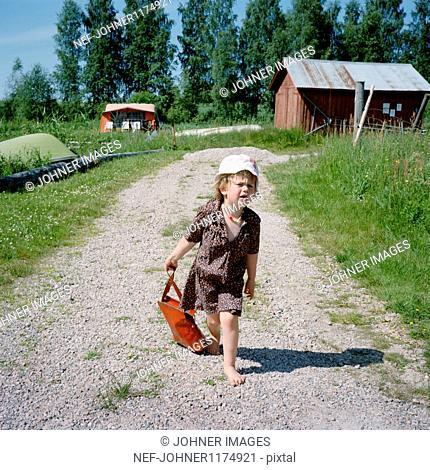 Girl pulling handbag through dirt track