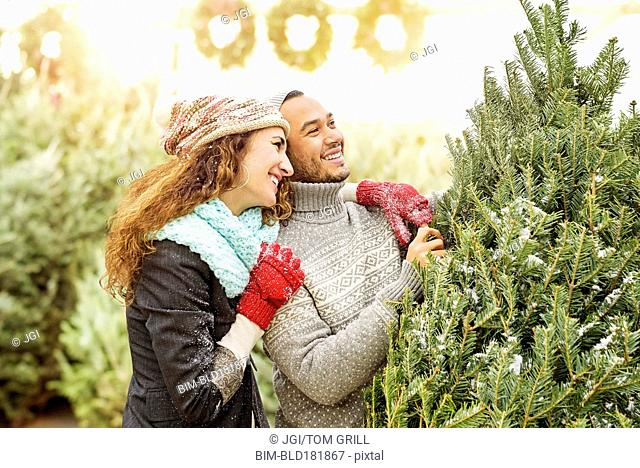 Couple hugging at Christmas tree farm