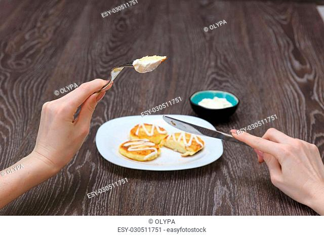 Girl eats cottage cheese pancakes, homemade traditional Ukrainian and Russian syrniki. Woman with piece of mini pancake, knife and fork in arms