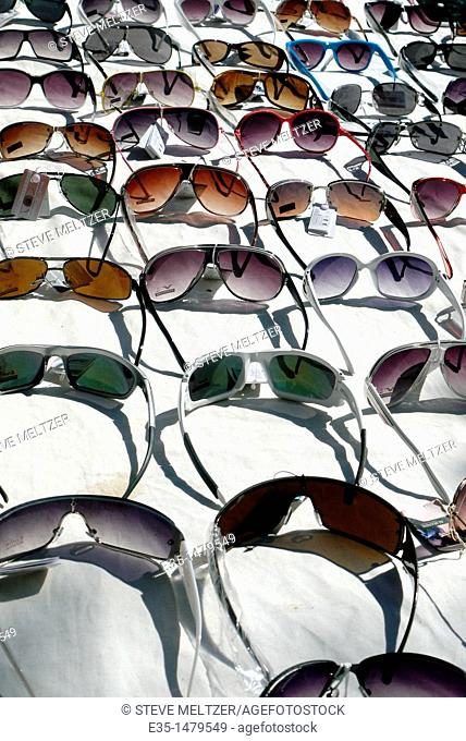 An assortment of sunglasses for sale at an outdoor market