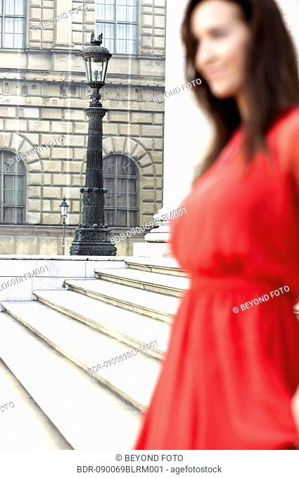 young woman in red dress standing in front of theatre