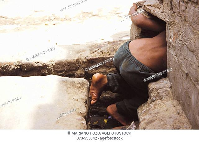 A child looking for water in a sewer. New Delhi, India