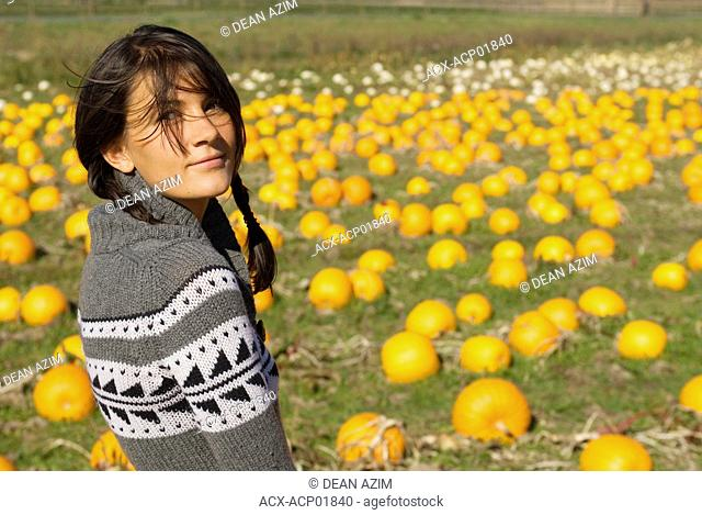 A young woman in a pumpkin field, Vancouver Island, British Columbia, Canada