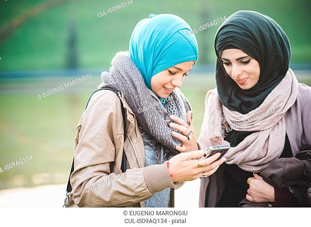 Two young women at lakeside texting on smartphone