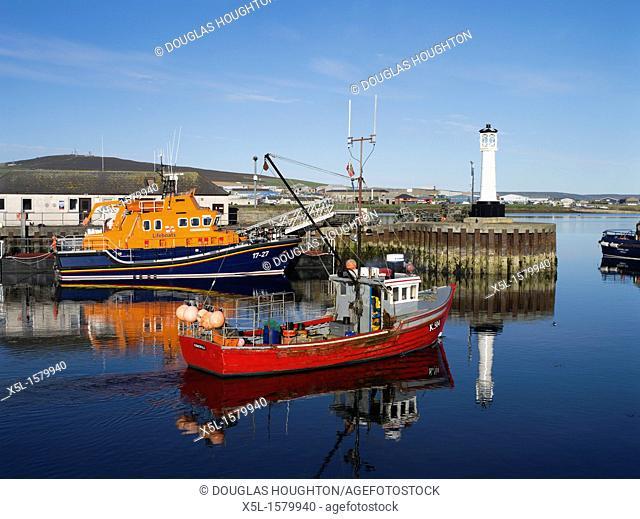 Kirkwall harbour KIRKWALL ORKNEY Red crab boat leaving harbour lifeboat RNLB Volunteer Spirit at quay