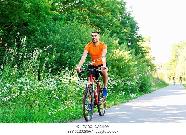 fitness, sport, people and healthy lifestyle concept - happy young man riding bicycle outdoors