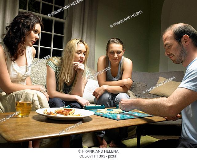 Four young people playing scrabble