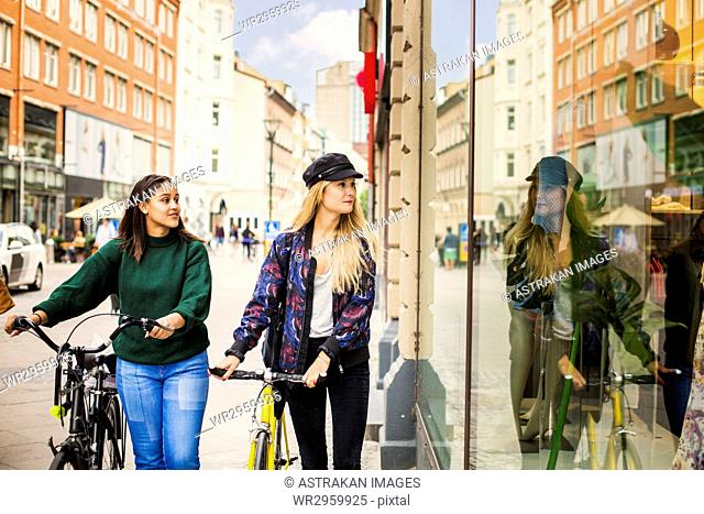 Two young women with bicycles looking at store window