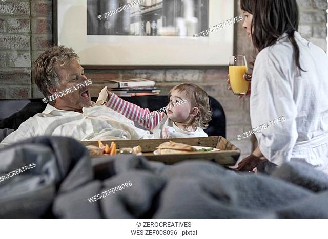 Family having breakfast together in bedroom