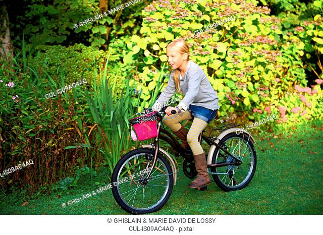 Young girl riding bicycle in garden