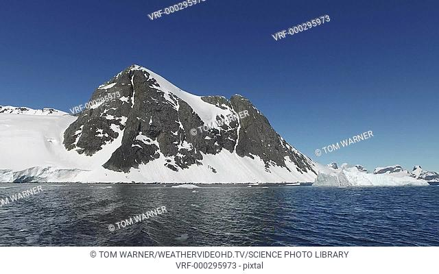 Snow-covered glaciers and mountains on the Antarctic peninsula, with icebergs in the Southern Ocean in the foreground