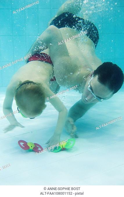 Father helping boy swim to bottom of pool to retrieve toy