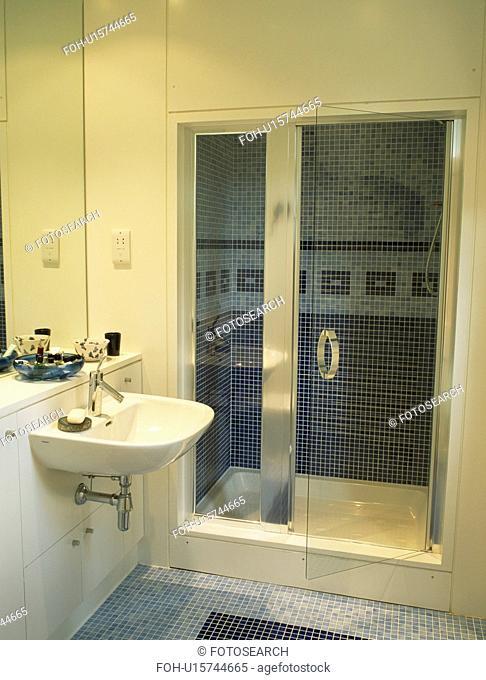 Glass doors on shower cabinet in modern white bathroom