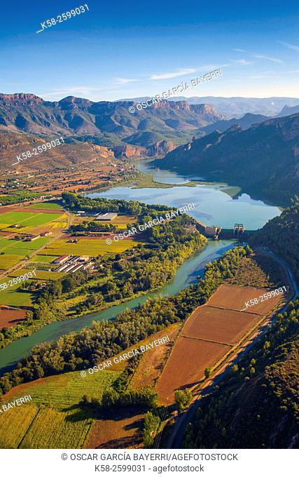 Aerial view of river Segre and the Sant Llorenç de Montgai village and reservoir passing through the fields, Montsec mountain range, pre-Pyrenees mountains