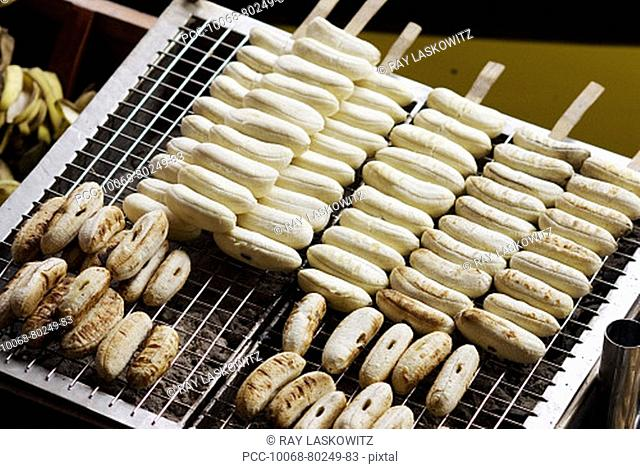 Thailand, Bangkok, unusual delicacies found at street vendor food stalls, closeup of bananas cooking on the grill