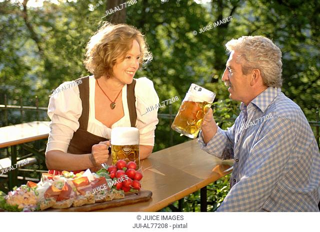 View of a middle aged couple drinking beer, beergarden, Munich, Bavaria, Germany
