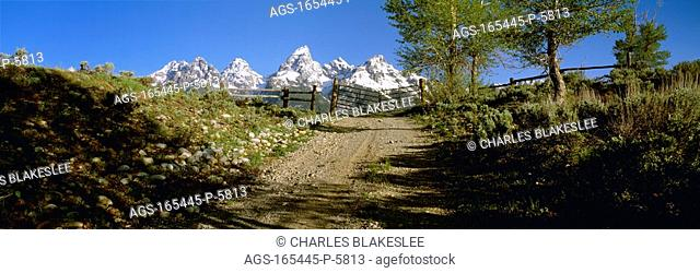 Agriculture - Gravel ranch road and gate, with the snow capped Grand Teton mountains in the background / WY - Teton County
