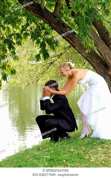 Couple romancing by side of lake, newlywed bride and groom