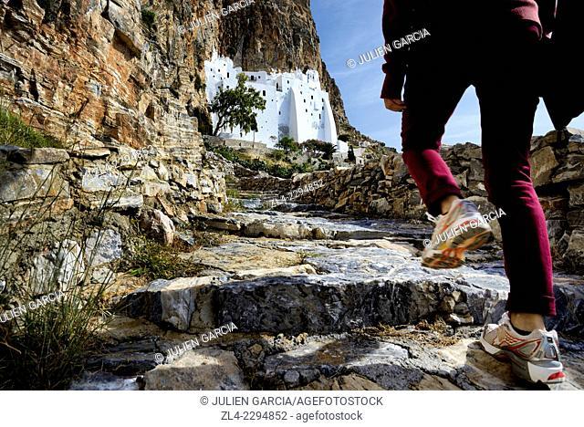 Woman's leg climbing up the trail to the monastery of Panagia Hozoviotissa Moni Hozoviotissis, Chozoviotissa. Greece, Greek islands in the Aegean sea