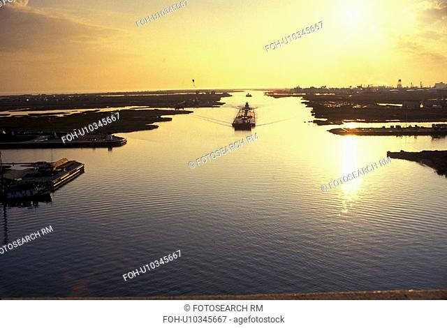 Barge in Inland Waterway with Sun Reflection in Water