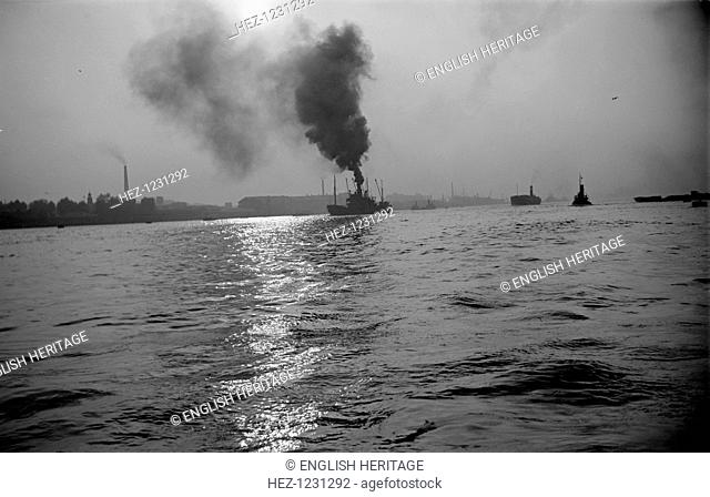 Shipping in Greenwich Reach on the River Thames, London, c1945-c1965. A vessel lets off clouds of smoke on an overcast day