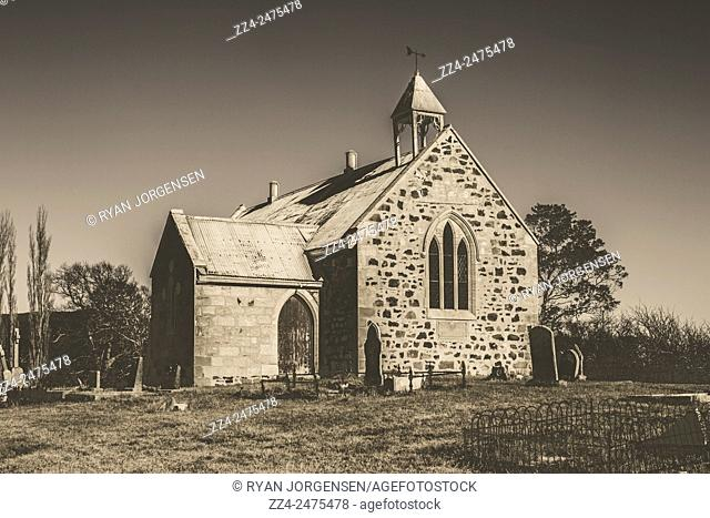 Vintage washed out photo of an old toned western church built with stones and cement. St Marys, Tasmania, Australia