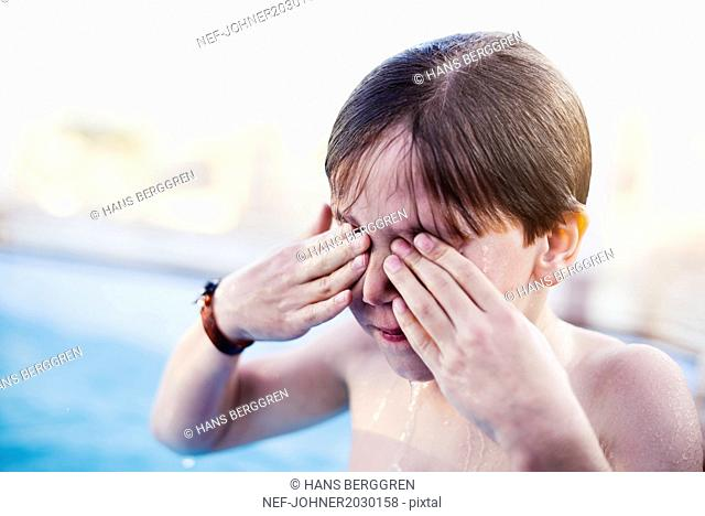 Boy with hands covering eyes