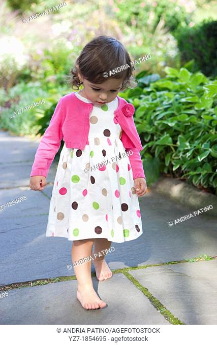 20 Month old girl in poka dots dress with pink cardigan sweater walking bare foot over pavers in garden