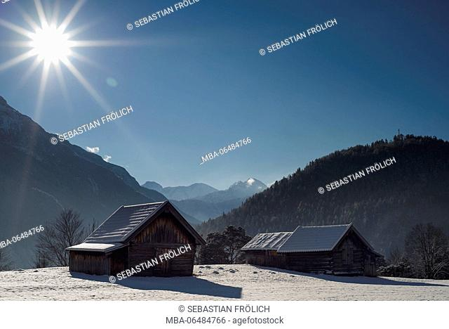Snow-covered meadow with reflective snowflakes and two hay stacks with the sun and nice sunrays, in the background the mountains