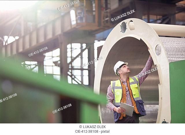Male engineer with clipboard examining steel pipe in factory