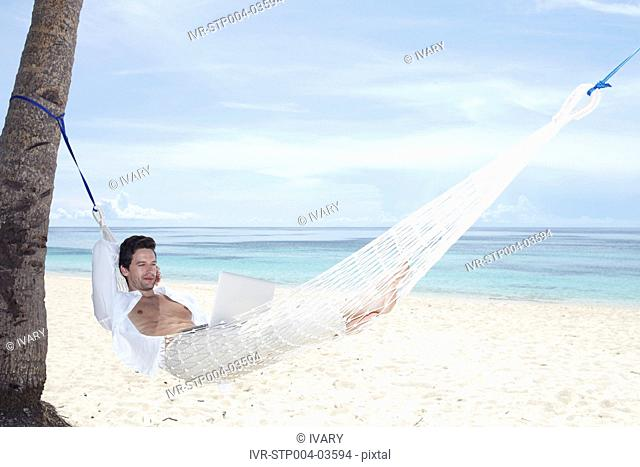 A man relaxing in a hammock with a laptop