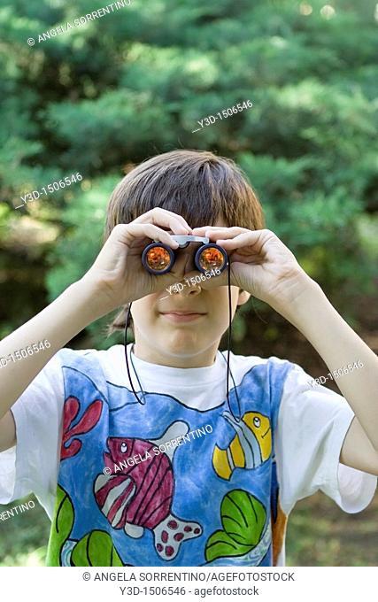 Boy looking through a pair of binoculars