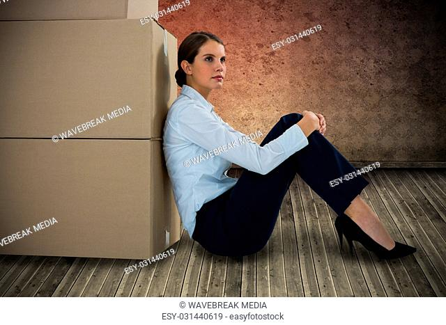 Composite image of businesswoman leaning on cardboard boxes against white background