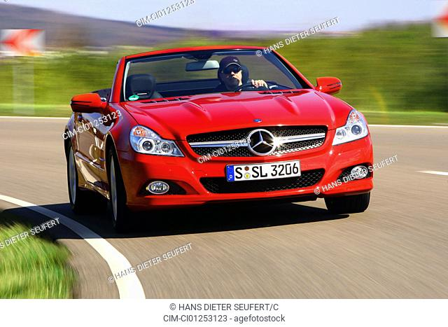 Mercedes SL 350, model year 2008-, red, driving, diagonal from the front, frontal view, country road, open top