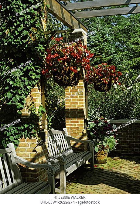 GARDENS: Overhead pergola, hanging baskets, two wooden benches between brick columns, brick patio, climbing vines