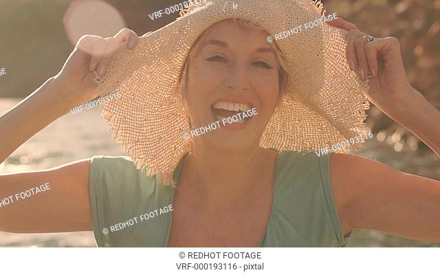 Dolly shot of woman sitting and relaxing on jetty at lakeside with hat laughing