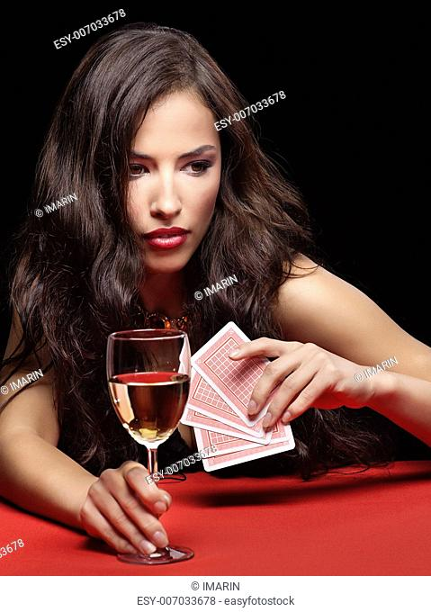 pretty young woman holding gambling cards and glass of wine on red table