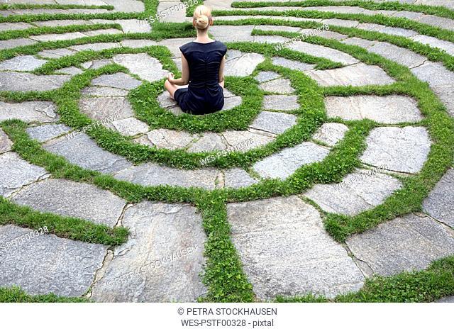 Italy, Alto Adige, Lana, woman sitting in natural open air maze meditating