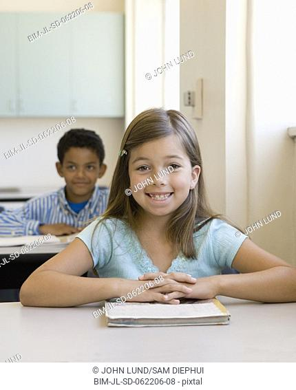 Young girl smiling at desk in classroom