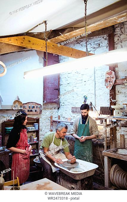 Team of potters in illuminated workshop