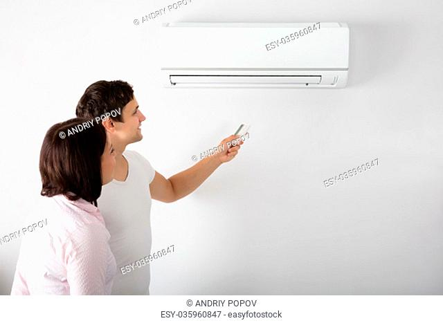 Happy Young Couple Adjusting Temperature Of Air Conditioner By Remote