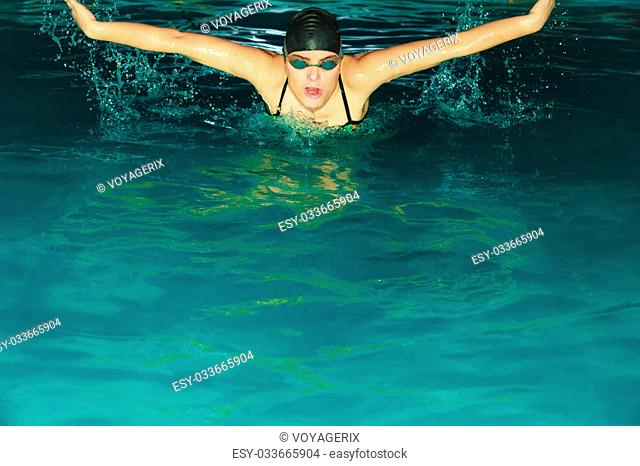 Woman athlete swimming performing butterfly style stroke in pool. Active human swimmer taking breath. Water sport comptetition